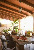 A patio table laid for a Mediterranean snack on the veranda under a wooden roof