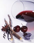 A glass of red wine lying on its side, with spices, cherries and candied violets
