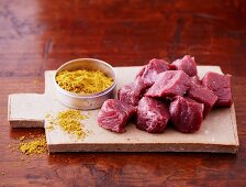 Diced lamb and curry powder on a wooden board