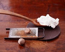 Quark on a wooden spoon and nutmeg on a grater
