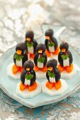 Olive penguins with cream cheese, carrots and radishes