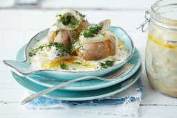 Jacket potatoes with pickled herring, onions and a sour cream sauce