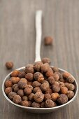 A spoon full of allspice berries