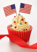 A cupcake decorated with US flags and a red ribbon