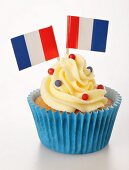 A cupcake decorated with buttercream and French flags