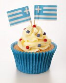 A cupcake decorated with buttercream and Greek flags