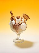 A nut sundae with vanilla and nut ice creams, cream, amarettini biscuits, wafers, nuts, meringues and butterscotch sauce