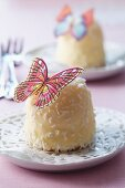 White marshmallow kiss decorated with grated coconut and with a butterfly made from edible paper