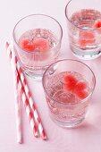 Wasser in Gläsern mit herzfömigen Eiswürfeln aus Fruchtsaft