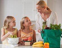 Mother with children (4-5) in kitchen, (focus on background)