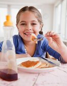 Young girl eating pancakes