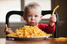 Toddler eating a large plate of French fries
