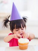 Portrait of baby girl (12-17 months) in party hat eating cupcake