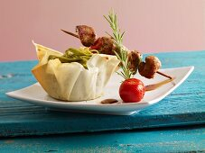 Meat kebabs with green tagliatelle in a phyllo basket