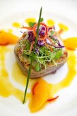 Grilled tuna steak with edible shoots and a fruity sauce