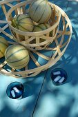 Melons in two wooden mesh baskets of different sizes on blue wooden table