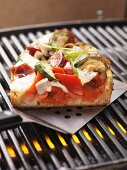 A slice of sausage, vegetable and mozzarella pizza cooked on the barbecue, on a spatula