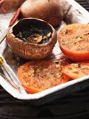 Barbecued portobello mushrooms and tomatoes in an aluminium tray