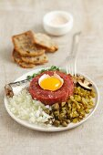 Classic beef tartar with egg, onion, pickled cucumber and mushrooms