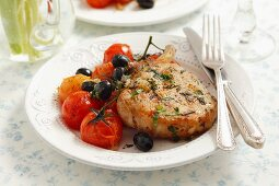 Pork chop with black olives and cherry tomatoes