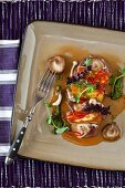 Fried halloumi on slices of cured sausage with mushroom sauce, peppers, herb sauce and lavender flowers
