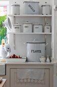 White, vintage enamel tins with lids on bracket shelves next to kitchen window