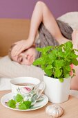 An ill woman lying in bed, with a teacup, fresh lemon balm, and a bulb of garlic