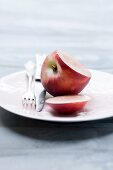 A nectarine, sliced open, on a plate