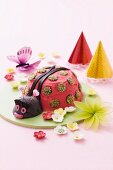 A child's birthday cake (a ladybird) and party decorations