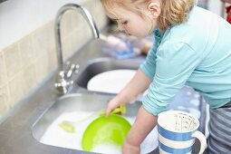 A girl washing up in the kitchen