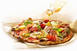 Olive oil being drizzled over a ham and vegetable pizza