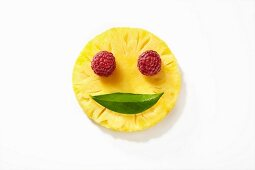 A smiling face made from pineapple, raspberries and a leaf