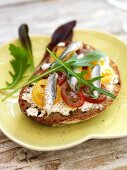 Bread topped with cream cheese, tomatoes and anchovies