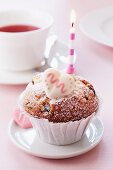 A muffin decorated with a candle and a sugar heart