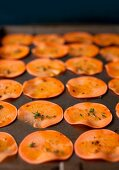 Sliced Sweet Potatoes with Herbs on a Baking Sheet