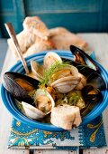 A Bowl of Mussel and Clam Stew with Fresh Dill and Bread