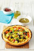 Puff pastry tart with tomatoes, leek, olives and basil pesto
