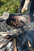 Chestnuts being roasted in an iron pan over an open fire