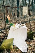 A table laid outdoors with vegetables and a tablecloth; in addition, there are fish hanging from a rustic wooden frame