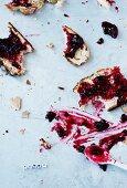 Partly eaten slices of raisin bread spread with cherry jam