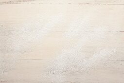 A wooden surface dusted with icing sugar