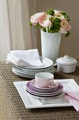 Stacked plates and coffee cups; in the background, a bunch of flowers with pink ranunculus
