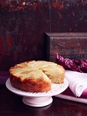 Pear cake with almonds on a white cake stand