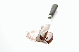 Melted cooking chocolate being spread with a palette knife