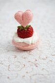 A rose macaroon topped with: cream, a fresh strawberry, and a heart-shaped strawberry macaroon