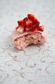 A rose macaroon topped with diced strawberries