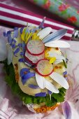 A slice of bread topped with butter, flower petals and radishes