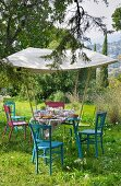 A table laid for a meal in the garden, under an awning