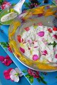 Cream cheese ice cream with geranium petals and basil coulis