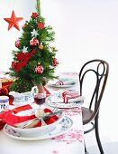 A table laid for Christmas dinner decorated with a mini Christmas tree